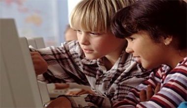 Blonde and Brown haired boys at a computer